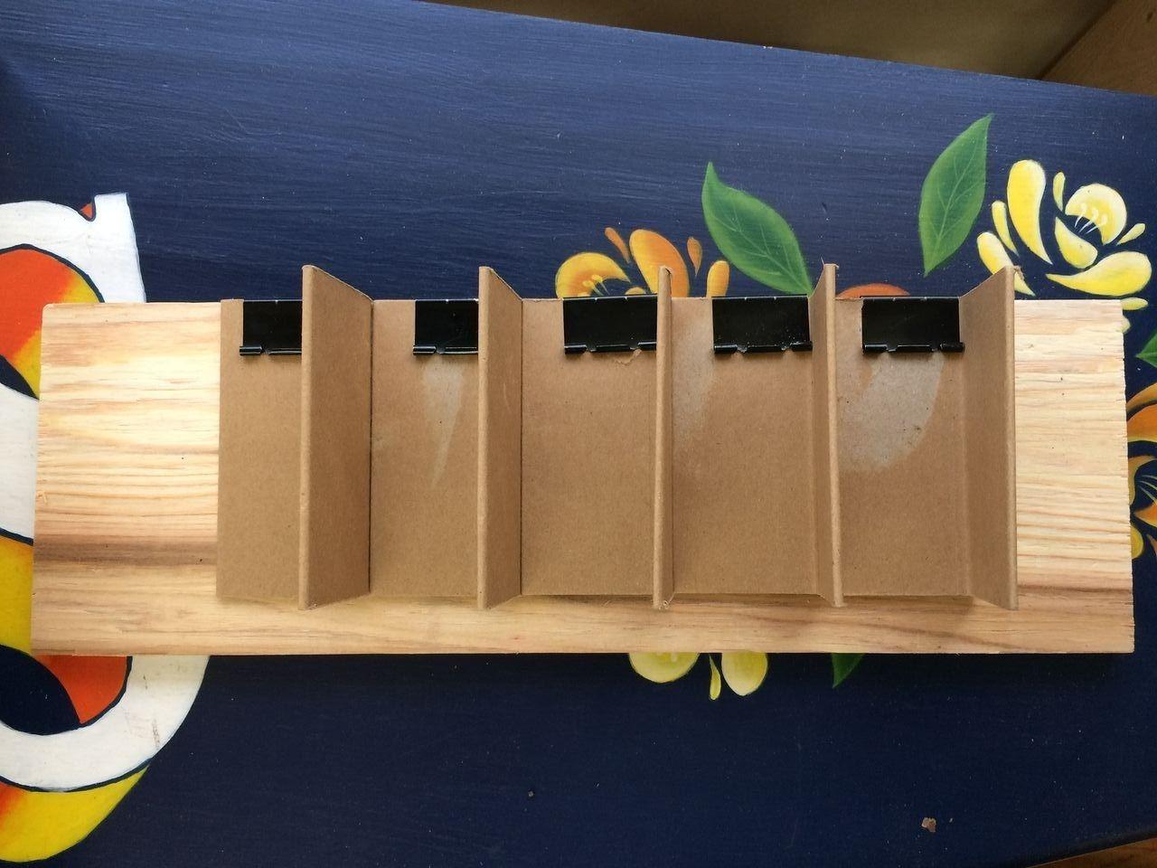自作の工具ホルダーの衝立(間仕切り)を裏板にダブル・クリップで取り付けたのち金具を外す。