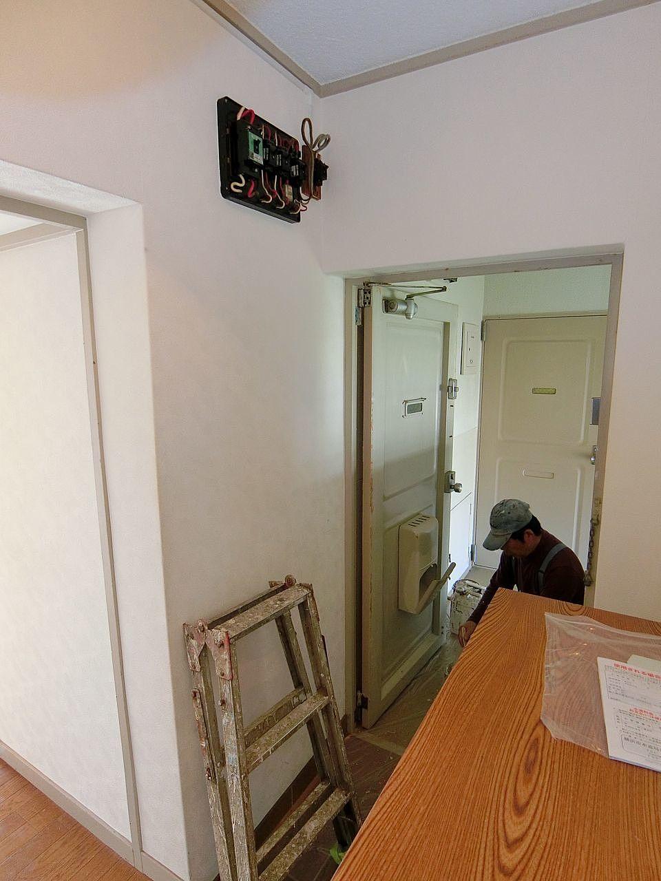 たまプラーザ団地の玄関ドアー内側のペンキ塗装作業中の職人さん